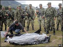Soldier removes a plastic bag from body of an alleged rebel in Urrao, southwest of Medellin, on 19 January while other soldiers look on