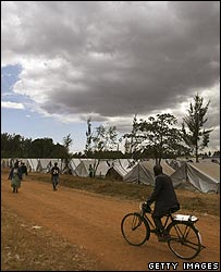 Man cycles past a camp for displaced Kenyans in Eldoret