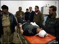 Iraqis stand next to a man at a hospital in Kirkuk who was injured by the blast in al-Dibis (23 January 2007)
