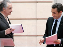 French economist Jacques Attali, left, hands French president Nicolas Sarkozy a copy of a report by the commission he heads, at the Elysee palace in Paris on 23 January 2008