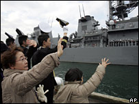 Relatives and sailors wave as the Murasame leaves port