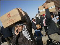 Palestinians carrying cigarette cartons