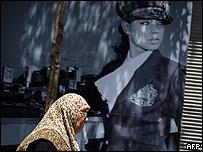امرأة ترتدي الحجاب تسير في اسطنبول وفي الخلفية ملصق إعلاني لفتاة عصرية، 16 يوليو/تموز 2007