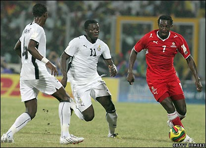 Collin Benjamin looks to take the ball past Sulley Muntari (c) and John Paintsil