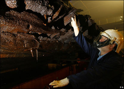 A workman examining the hull of the Mary Rose