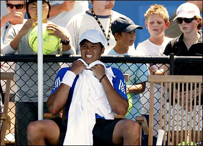Tsonga takes a break on the practice courts as young fans look on