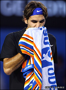 Federer wipes his face with a towel between games