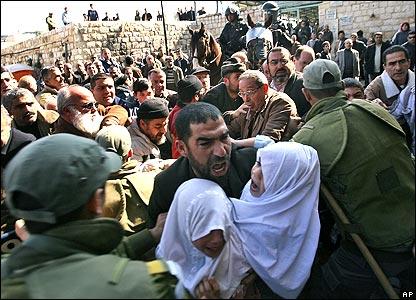 Man carrying frightened girls through crowd