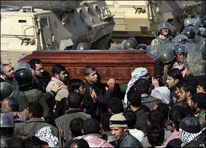 Palestinian carry a coffin past Egyptian riot police at the Rafah border crossing, 25 January 2008