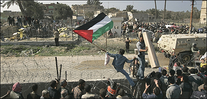 Palestinos cruzan la frontera con Egipto.