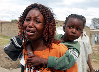 A woman cries while carrying a child on her back as they try to flee the violence in Nakuru