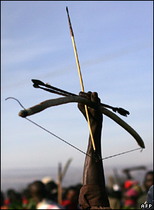 A member of the Luo tribe raises his bow and arrow during the clashes in Nakuru