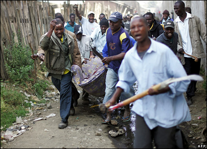 Members of the Luo community carry a wounded man who was attacked by a crowd of Kikuyus during the clashes in Nakuru