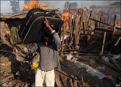 A man carries some of his belongings past a house set alight by supporters of Raila Odinga during the unrest in Nakuru