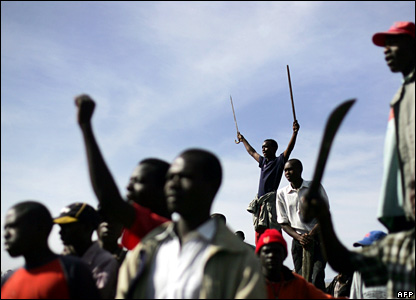 Supporters of Raila Odinga wave machetes and sticks as they gather in a field during the clashes in Nakuru