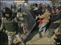 Egyptian riot police try to prevent Palestinians from crossing the border