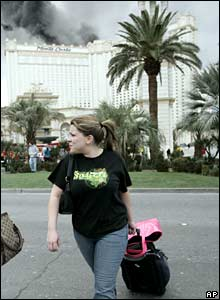 Californian Melissa Franco, who had been staying at the Monte Carlo hotel and casino, carries her luggage away from the building