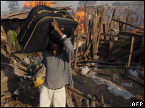 A man carries a suitcase from a fire set by an angry mob in Nakuru 25.01.08