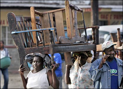 Kenyan women carrying their furniture arrive at a church in Nakuru 26/1/08