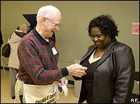 """A poll worker gives an """"I voted"""" sticker to a voter in Simpsonville, South Carolina"""