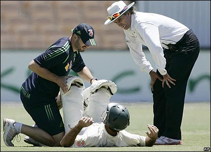 Ricky Ponting is treated by physio Alex Kountouris for back spasms, watched on by umpire Billy Bowden