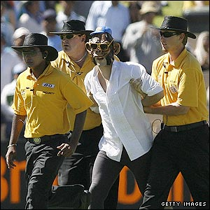 A spectator wearing a monkey masks is led off after invading the field of play