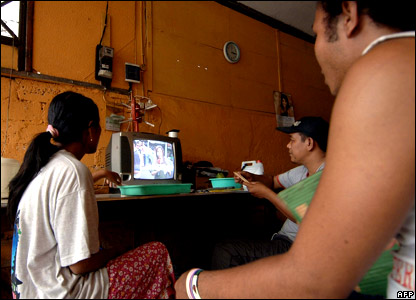 Residents watch television reporting of the death in Jimbaran on Bali island.
