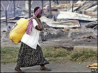 A Kikuyu woman walks past houses burned to the ground during ethnic clashes
