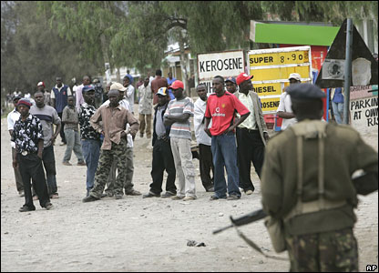 A soldier looks at a group of Kikuyu men patrolling the streets of Naivasha on Sunday