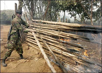 A Kenyan policeman pulls apart a burning fence close to a group of torched houses in the rural village of Banita, Kenya on Sunday