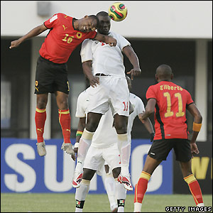 Angola's Flavio rises for a header