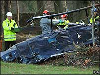 Workers examine the helicopter crash scene