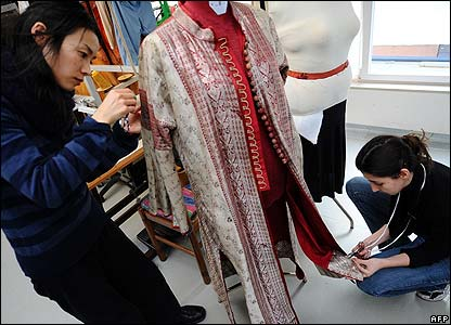 Employees of Venetian designer Stefano Nicolao make adjustments to costumes