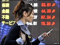 A woman passes a share prices board in Tokyo (image from 25 January)