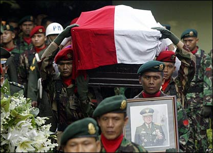 Soldiers carry Suharto's flag-draped coffin from his residence