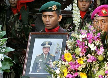 A soldier holds a picture of former Indonesian leader Suharto