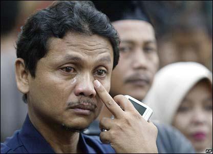 Seorang pria menitikkan air mata ketika konvoi duka mendiang Suharto melintas