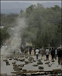 Kikuyu men walk past makeshift roadblocks in Naivasha