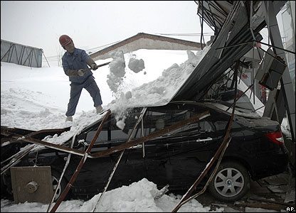 Worker shovels snow from collapsed car showroom, Wuhan, 28 Jan 2008