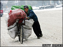 A man pushes a bicycle loaded with goods through snow in Wuhan, Hubei province on 27 January 2007