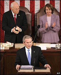 President Bush standing in front of Vice-President Cheney and Nancy Pelosi