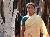 A Hindu woman walks through her destroyed village