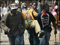 Wounded Kikuyu man being carried away from Kibera slum