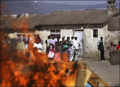 Residents of a Naivasha neighbourhood watch as property burns on a fire set by a Kikuyu mob (29/01/2008)