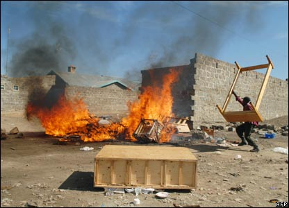 A Kikuyu man throws a bed frame on to a fire in Naivasha (29/01/2008)