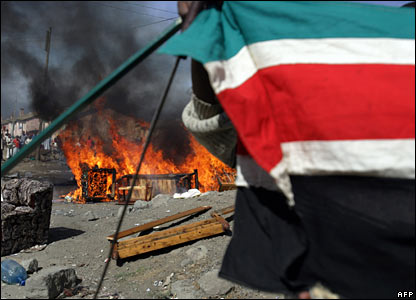 A member of the Kikuyu tribe displays a Kenyan flag next to a fire in Naivasha (29/01/2008)