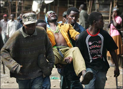 An injured Kikuyu man is carried to safety in the Kibera slum area of Nairobi (29/01/2008)