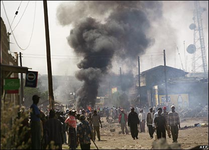 Groups of Kikuyu men walk through the streets of Naivasha, while smoke plumes in the background (29/01/2008)