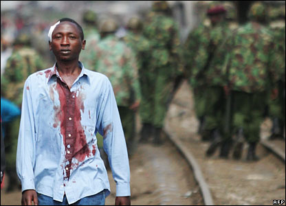 A member of the Kikuyu tribe walks away from police with his shirt covered in blood, Kibera, Nairobi (29/01/2008)
