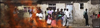 Naivasha residents watch a house burn that was set alight by Kikuyu gangs